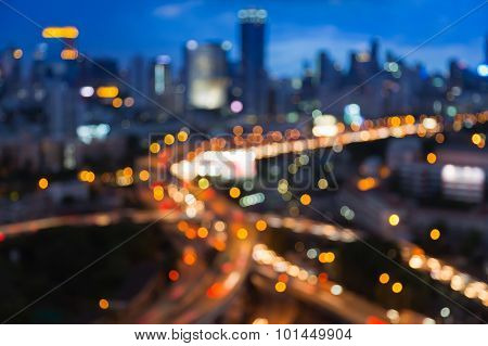 Blurred bokeh lights of city freeway intersection with city background