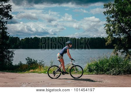 girl mountainbiker rides along lake