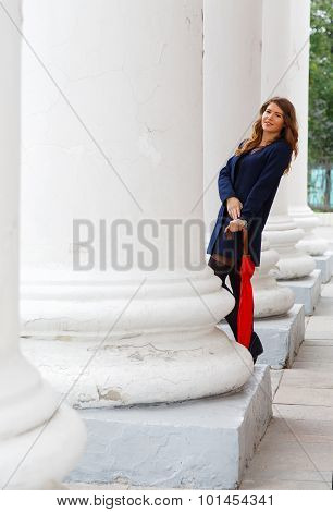 Girl With A Red Umbrella On A Background Of Pillars