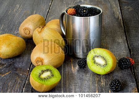 Fresh Kiwi And Blackberries On A Wooden Table, Sliced Kiwi Fruit.