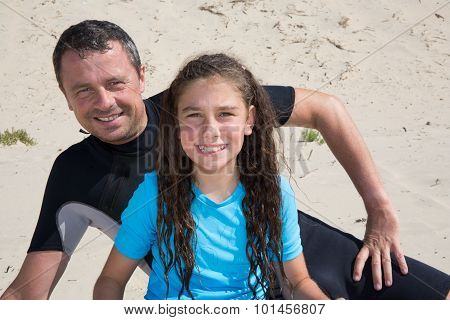 Man And Girl In Wetsuit On A Sunny Day At The Beach
