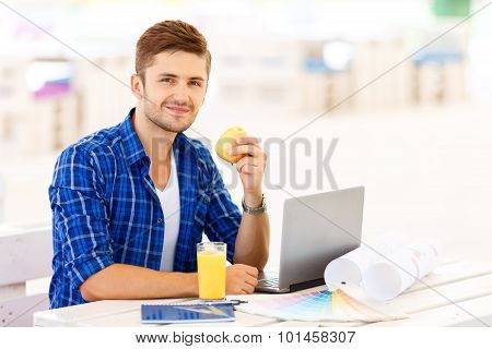 Overjoyed freelancer sitting at the table