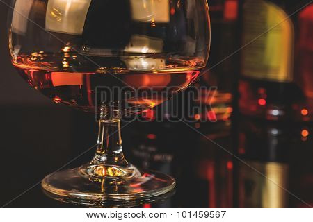 Snifter Of Brandy In Elegant Typical Cognac Glass In Front Of Bottles In Background
