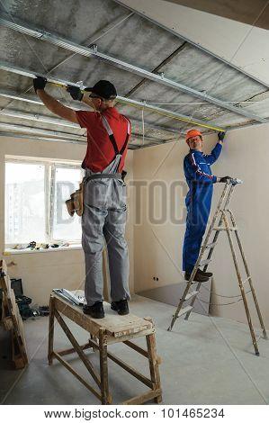 Workers Measure Metal Frame