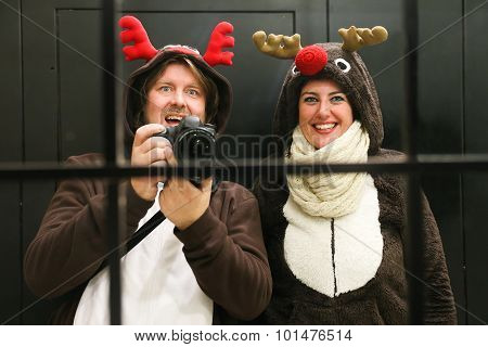 Young Couple Dressed Up As Two Reindeer Taking A Selfie