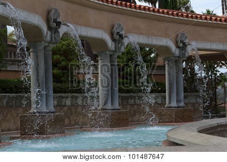 Fountain flows from the top of an arch into a blue pond