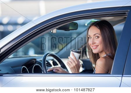 Cute young woman is driving a vehicle with hot drink