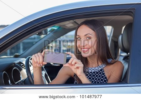 Beautiful female driver is making photos on telephone