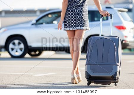 Cheerful young girl is moving to her vehicle