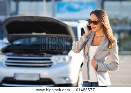 Beautiful fit businesswoman is communicating on telephone near transport