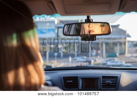 Beautiful young woman is doing make-up in transport