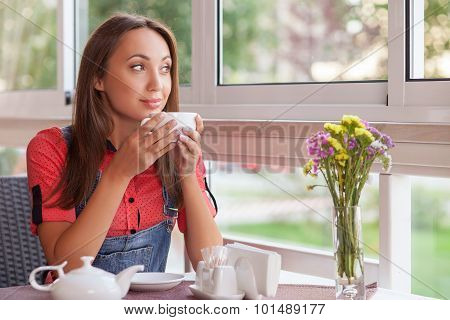 Beautiful young woman is enjoying hot drink in cafeteria