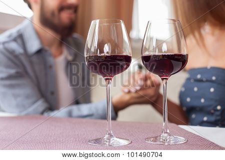 Pretty young loving couple is dating in restaurant