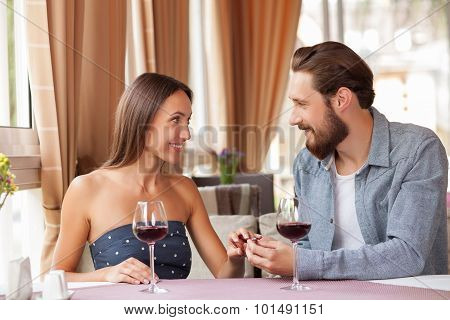 Attractive young loving couple is celebrating in restaurant