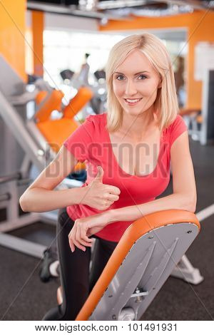 Cheerful young girl is training in fitness center