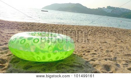 Green lifebelt, sea and beach