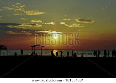 Sunset silhouette of people playing at the beach