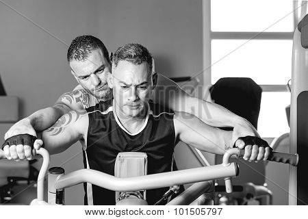 Personal Trainer Helping Man With Shoulder Exercise.