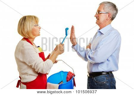Senior couple with cleaning supplies having discussion over chores