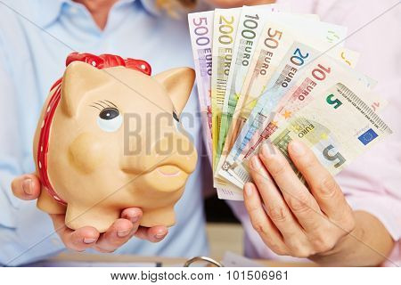 Two hands holding a piggy bank with Euro money bills