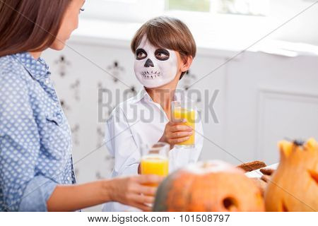 Beautiful woman and child are making fun on Halloween