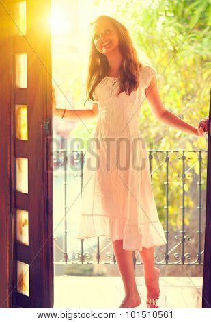 Beauty teenage girl in the white dress standing in the open doorway balcony. Happy teen girl standing on the balcony of her house in sunlight and smiling. Happiness. Full-length photo