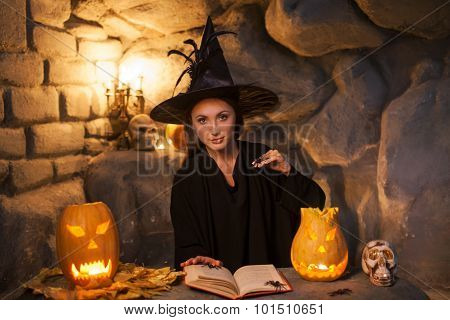 Cheerful young witch is conjuring in Nut-Crack Night