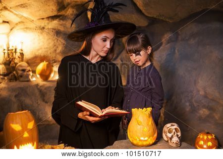 Cheerful female wizard is teaching child to conjure