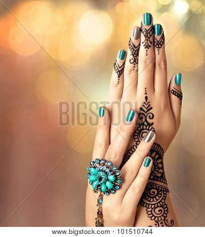 Woman Hands with black mehndi tattoo. Hands of Indian bride girl with black henna tattoos. Hand with perfect turquoise manicure and national Indian jewels. Fashion. India. Marriage traditions