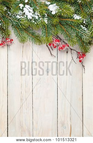 Christmas wooden background with fir tree and holly berry. View from above with copy space