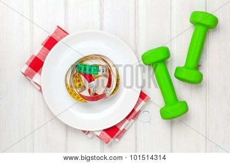 Dumbells and tape measure on plate over wooden background. View from above
