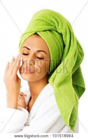 Spa woman in bathrobe removing makeup.