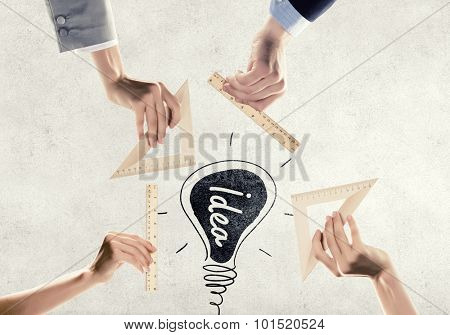 Close up of people hands measuring ight bulb with ruler