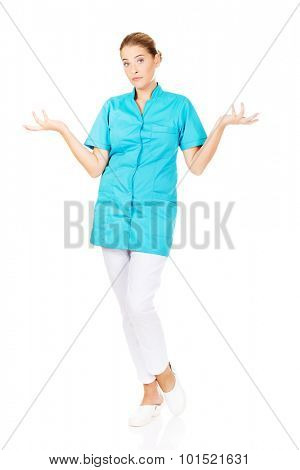 Young female doctor or nurse shrugs.