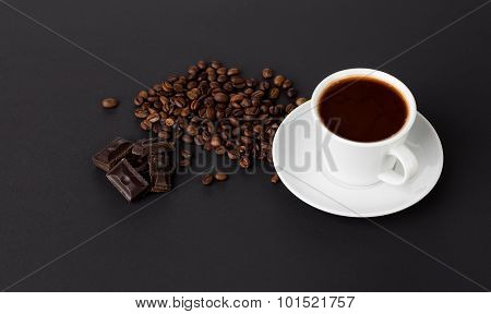 Cup of coffee with chocolate and beans