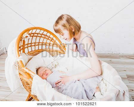 Little baby sleeps in cradle and her older sister looking at her