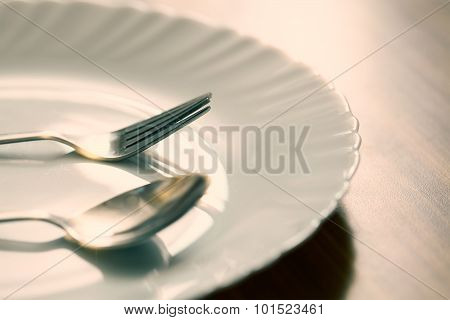 Fork and spoon with white plate.