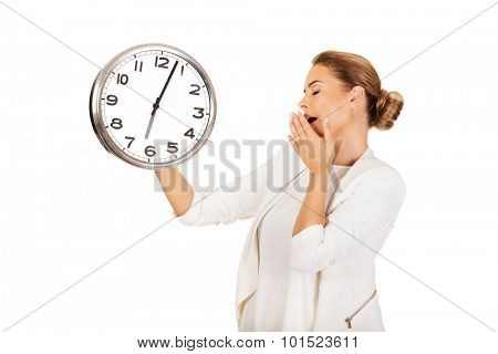 Yawning businesswoman with a clock.