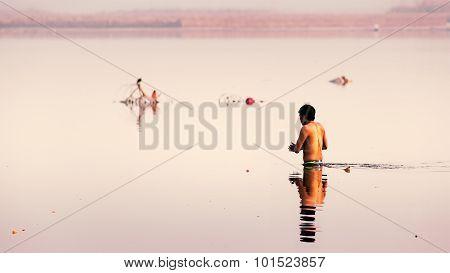 An Indian man taking holy dip.