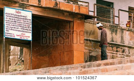 An adult man urinating in public.