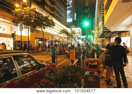 View of busy street and shops of Hong Kong at night.