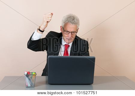 Senior man angry while working with laptop at the office