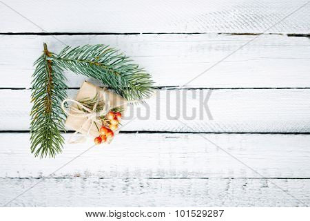 Gift in package and evergreen conifer branches over wooden background