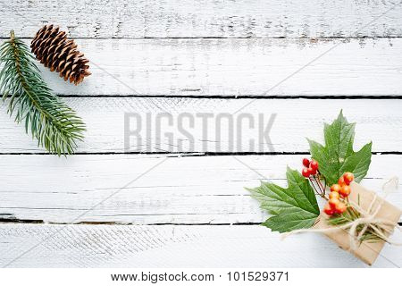 Gift in package, conifer branch, guilder leaves and berries over wooden background