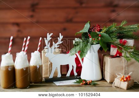 Toy deer, porcelain vase with guelder leaves and berries, bottles with hot chocolate topped with whipped cream and giftboxes on table in cafe