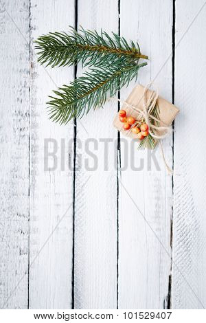 Small giftbox and two conifer branches over wooden background