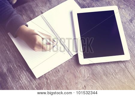 Girl Writing In A Notebook With A Digital Tablet