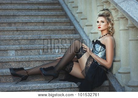 Girl In Old-fashioned Dress Sitting On The Stairs.
