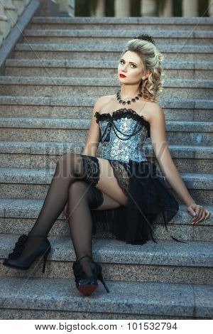 Girl In Dress Sitting On The Stairs.