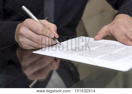 Hands of man signing formal paper